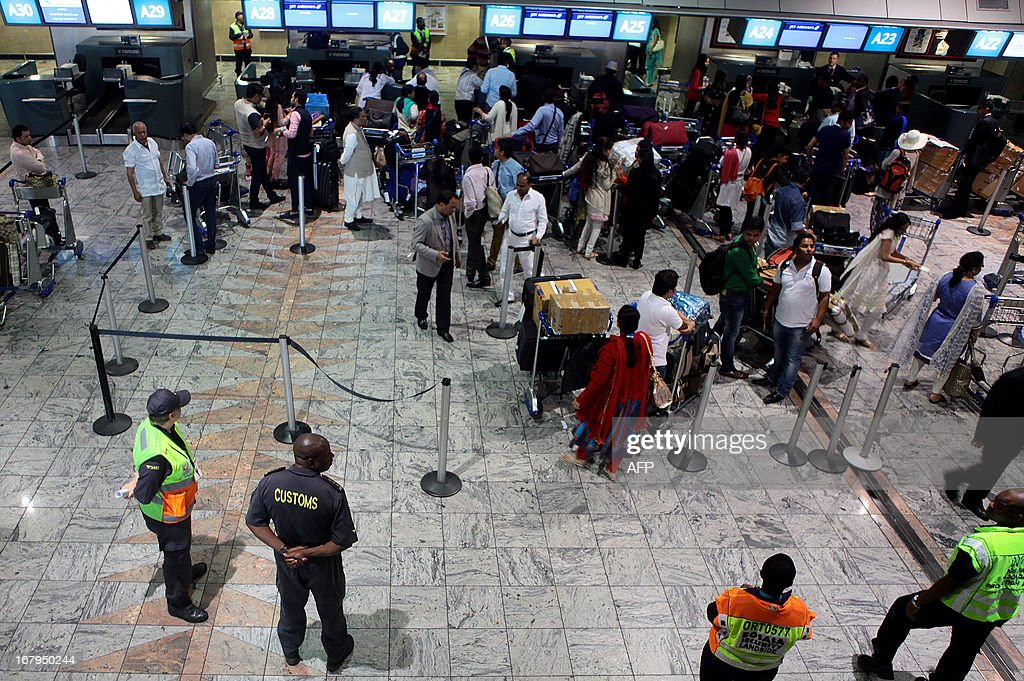 South African Customs officials watch as members of the Gupta wedding party check in at O. R. Tambo International Airport in Johannesburg for their flight back to India on May 3, 2013. The Gupta wedding made headlines after a plane carrying 180 wedding guests including Bollywood stars and Indian government ministers landed at Waterkloof Airforce Base in Pretoria and the guests were subsequently escorted by South African police to Sun City where the four-day wedding was to be held. Three South African government officials have since been suspended due to the incident. AFP PHOTO /JENNIFER BRUCE