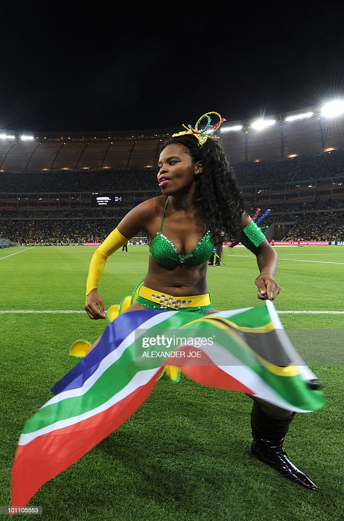 A South African dancer holds a national flag as she performs on the pitch during the friendly football match between South Africa and Colombia at Soccer City Stadium in Soweto, Johannesburg on May 27, 2010. The 2010 FIFA World Cup football championship is due to take place in South Africa from June 11 to July 11.