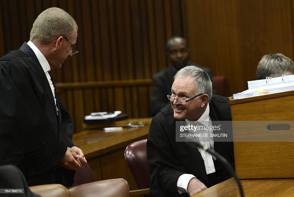 South African defence attorney Barry Roux (R) talks with South African Prosecutor Gerrie Nel on March 28, 2013 during the bail application appeal of South African Olympic sprinter Oscar Pistorius at the North Gauteng Hight Court in Pretoria. The court cleared Pistorius for international travel after the Paralympian sprint star, charged with murdering his girlfriend, challenged his stringent bail terms. Pistorius, 26, had appealed against a raft of conditions including the confiscation of his passport that he said were unfair and unwarranted. The double amputee, who faces trial later this year over the Valentine's Day killing of his model girlfriend Reena Steenkamp, was not in court for the appeal, which was opposed by the state.