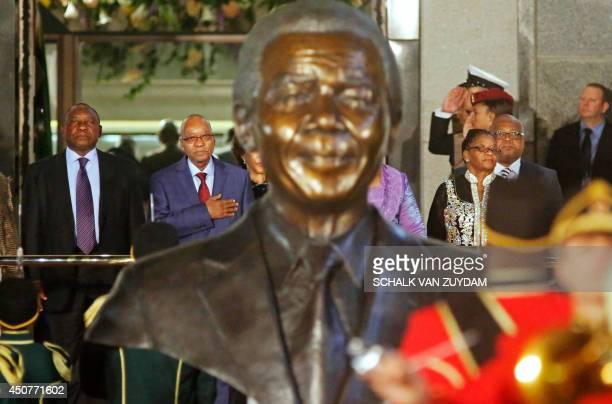 South African Deputy President Cyril Ramaphosa stands next to South African President Jacob Zuma with a bust of former South African President Nelson...