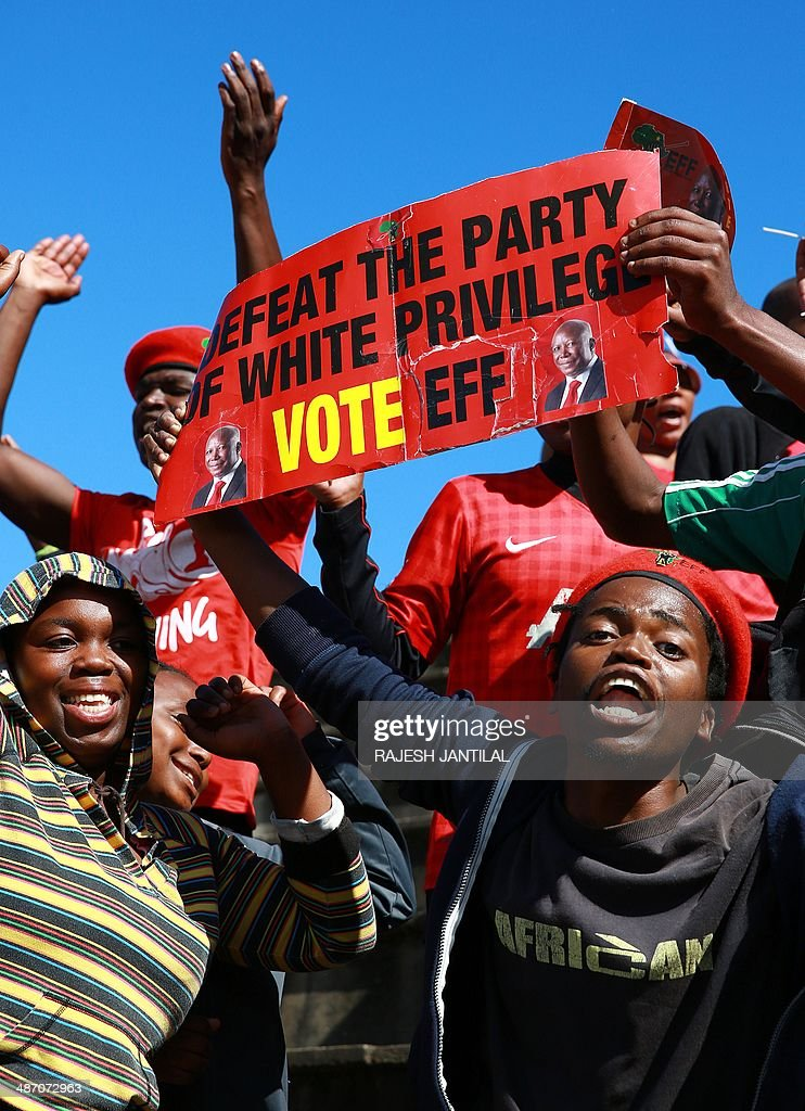 South African Economic Freedom Fighters (EFF) party supporters hold a sign and shout slogans during an election campaign rally in Umlazi, south of Durban, South Africa, on April 27, 2014. South Africans are going to the polls for a general election on May 7, 2014.