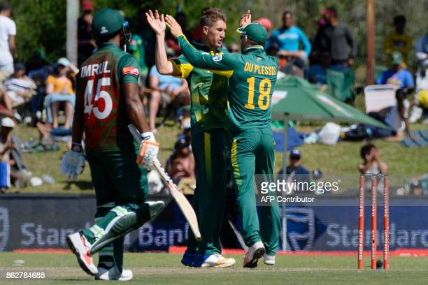 South African Faf du Plessis congratulates Dwaine Pretorius for taking the wicket of Bangladesh's Imrul Kayes during the second one day international...