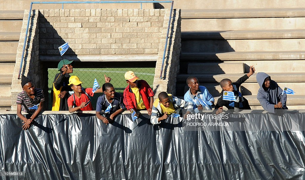 South African fans hold Uruguayan flags during a training sesion of the Uruguayan national football team in Kimberley on June 6, 2010. Uruguay will play their first match of the 2010 World Cup against France on June 11 in Cape Town. AFP PHOTO / Rodrigo ARANGUA