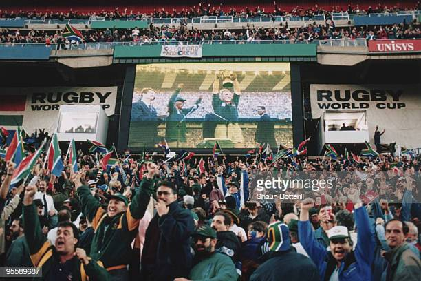 South African fans watch Francois Pienaar lift the trophy after South Africa defeated New Zealand in the Rugby World Cup final at Ellis Park...