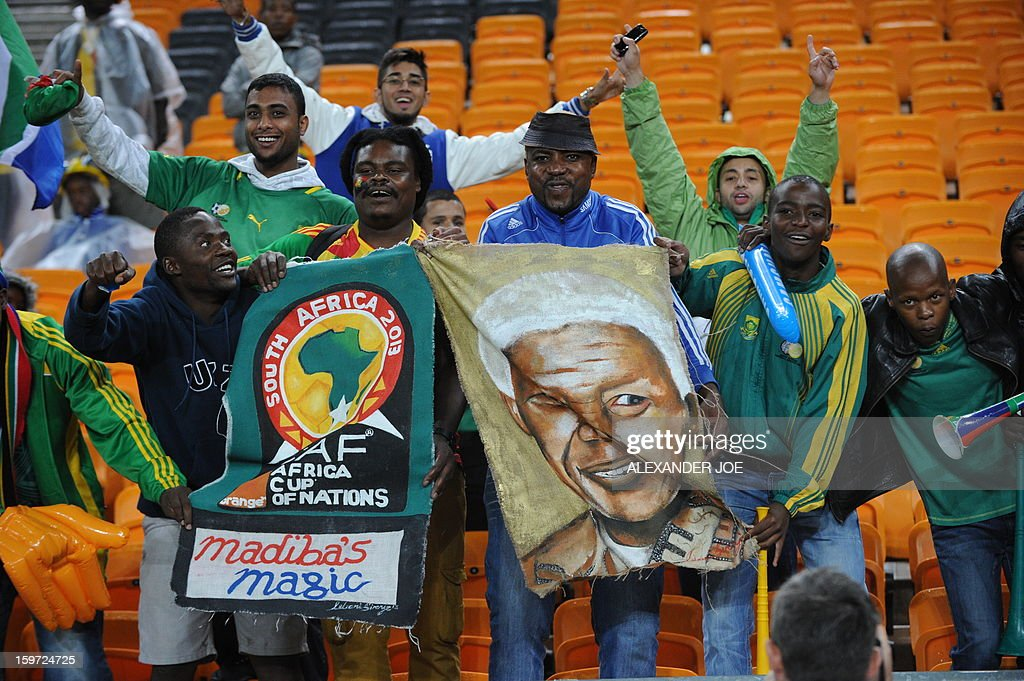 South African fans wave with a poster of former President Nelson Mandela during a group A football match against Cape Verde at the 2013 African Cup of Nations in Soweto on January 19, 2013 at Soccer City.