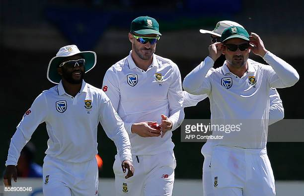 South African fielder Faf du Plessis holds the ball as he celebrates with teammates after taking a catch off the bowling of teammate Kagiso Rabada to...