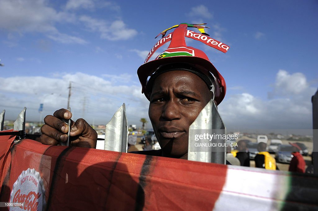 A South African football fan holds onto a gate as he waits to enter the O.R Tambo center and see the FIFA World Cup trophy after the unveiling on May 7, 2010 during the kick off of its South African tour in Kayelitsha on the outskirt of Cape Town, South Africa.