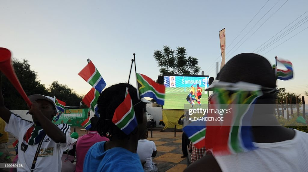 South African football fans celebrate a goal as they watch a Group D match between South Africa and Angola of the 2013 Africa Cup of Nations on a big TV screen in Rustenburg on January 23, 2013.