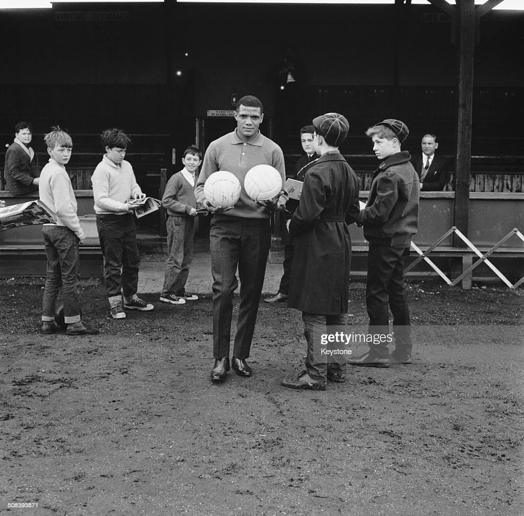 South African footballer Albert Johanneson of Leeds United with fans at the Hendon Football Club ground London during a team training session before...