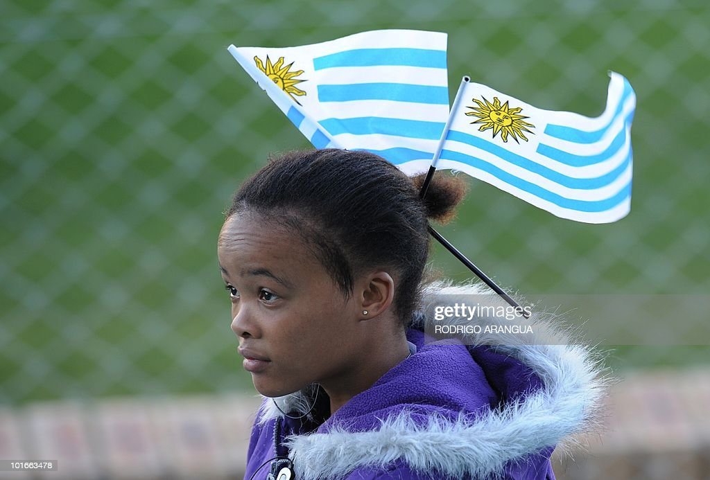 A South African girl carries Uruguayan flag on her very short pony tail during a training sesion of the Uruguayan national football team in Kimberley on June 6, 2010. Uruguay will play their first match of the 2010 World Cup against France on June 11 in Cape Town. AFP PHOTO / Rodrigo ARANGUA