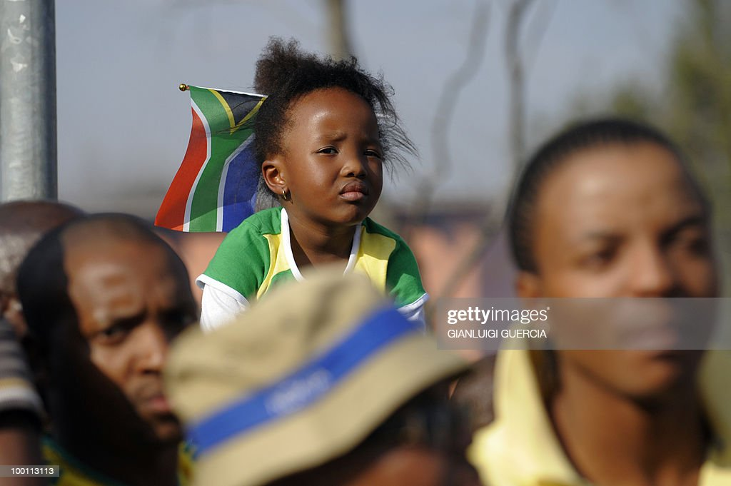 A South African girl looks at the concert with local artists performing on May 21, 2010 during the official celebration marking 20 days ahead of the FIFA WC2010 kick off at Vilakazi street in Soweto, South Africa. South Africa will host the FIFA World Cup from the 11 of June to the 11 of July, 2010.
