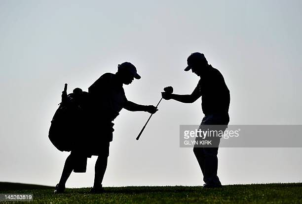 South African golfer Branden Grace exchanges clubs with his caddy on the 1st hole during the second round of the PGA Championship at Wentworth Golf...