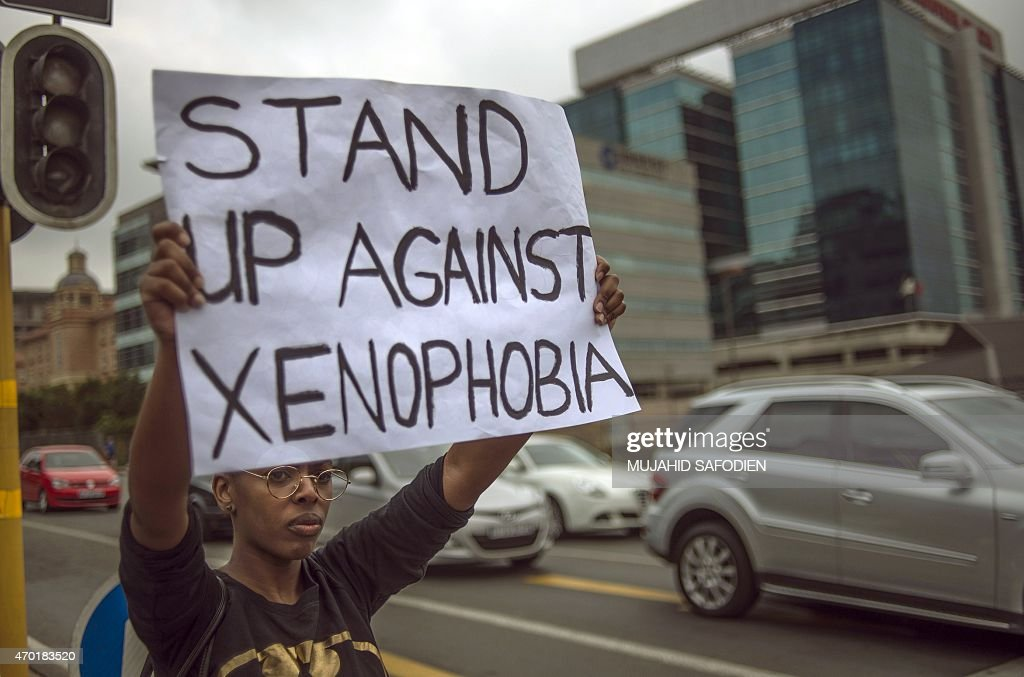 A South African holds a sign as she stands on the side od a road in Sandton as xenophobic violence continued on April 18 2015 South African police...