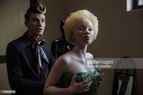 RENAUD South African lawyer and parttime fashion model Thando Hopa an albino tries on an evening dress by South African fashion designer GertJohan...