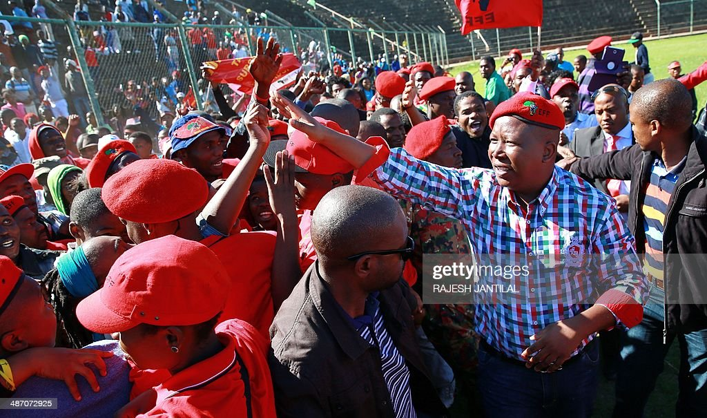 South African leader of the Economic Freedom Fighters (EFF) party and former African National Congress (ANC) Youth League leader Julius Malema (2nd R) greets supporters during an election campaign rally in Umlazi, south of Durban, South Africa, on April 27, 2014. South Africans are going to the polls for a general election on May 7, 2014.