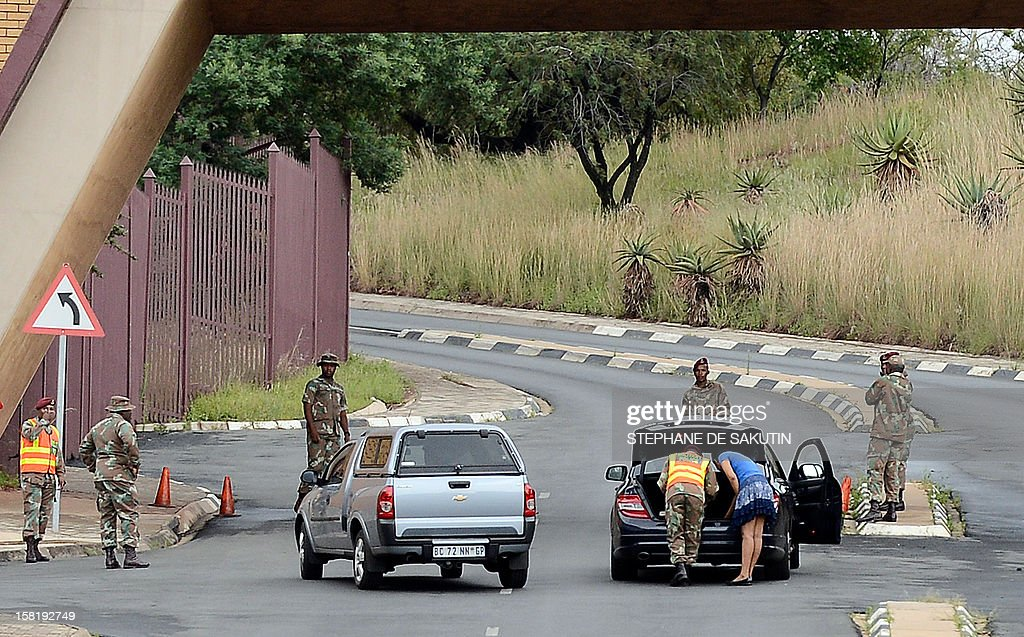 South African military police officers check cars entering the 1 Military Hospital in Pretoria where South Africa's former President Nelson Mandela is hospitalised on December 11, 2012. Nelson Mandela has a lung infection but is responding to treatment, the South African government said today, as the revered anti-apartheid icon spent his fourth day in hospital. AFP PHOTO / STEPHANE DE SAKUTIN