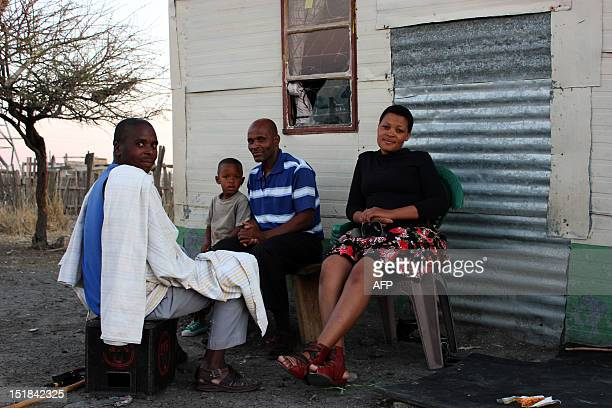 South African miner and his family sit outside their home in Marikana on September 9 2012 waiting for food handouts for the disaster relief...