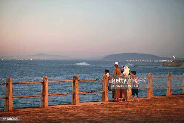 A South African muslim family stand at sunset on the beach front in Cape Town on June 28 as they try to spot the new moon signalling the commencement...