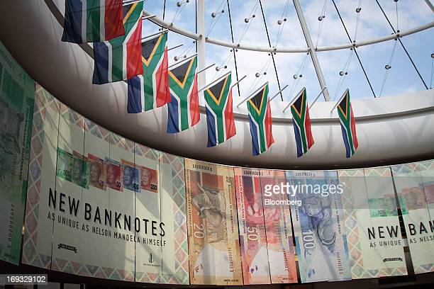 South African national flags hang above an advertisement for the new Mandela rand banknotes at the headquarters of the central bank in Pretoria South...