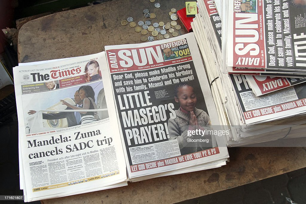 South African newspapers with headlines reporting on the health of the former South African president Nelson Mandela are laid out for sale on a street stall in Johannesburg, South Africa, on Thursday, June 27, 2013. South African President Jacob Zuma cancelled a trip to neighbouring Mozambique today after visiting Nelson Mandela, who remains critically ill in the hospital. Photographer: Nadine Hutton/Bloomberg via Getty Images