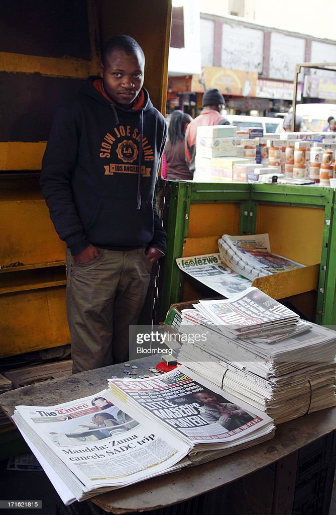 South African newspapers with headlines reporting on the health of former South African president Nelson Mandela are laid out for sale on a street stall in Johannesburg, South Africa, on Thursday, June 27, 2013. South African President Jacob Zuma cancelled a trip to neighbouring Mozambique today after visiting Nelson Mandela, who remains critically ill in the hospital. Photographer: Nadine Hutton/Bloomberg via Getty Images