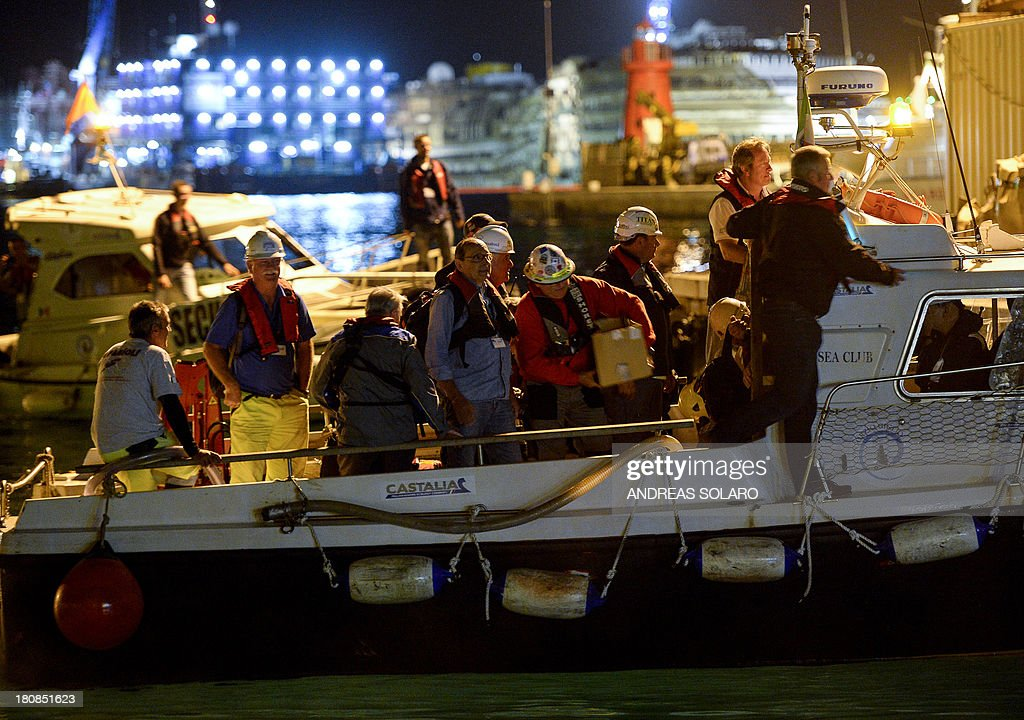 South African Nick Sloan (2nd R), senior salvage master for Titan-Micoperi, disembarks with his workers following the rotation of the wreck of Italy's Costa Concordia cruise ship on September 17, 2013 near the harbour of Giglio Porto. Salvage operators in Italy lifted the Costa Concordia cruise ship upright from its watery grave off the island of Giglio on September 17 in the biggest ever project of its kind.