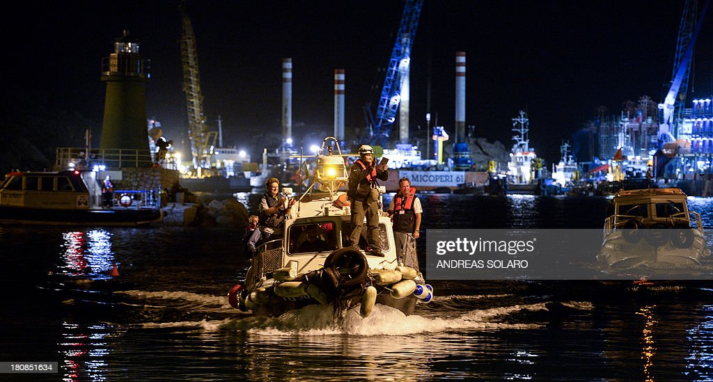 South African Nick Sloan (2nd R), senior salvage master for Titan-Micoperi, disembarks with his workers following the rotation of the wreck of Italy's Costa Concordia cruise ship on September 17, 2013 near the harbour of Giglio Porto. Salvage operators in Italy lifted the Costa Concordia cruise ship upright from its watery grave off the island of Giglio on September 17 in the biggest ever project of its kind. AFP PHOTO / ANDREAS SOLARO