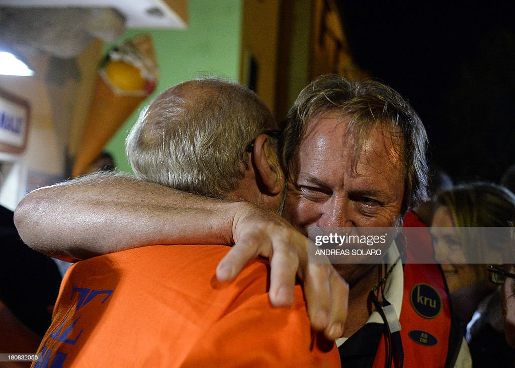 South African Nick Sloan (R), senior salvage master of Titan-Micoperi, embraces a worker following the rotation of the wreck of Italy's Costa Concordia cruise ship on September 17, 2013 near the harbour of Giglio Porto. Salvage operators in Italy lifted the Costa Concordia cruise ship upright from its watery grave off the island of Giglio in the biggest ever project of its kind. The ship's horn sounded for the first time since the January 13, 2012 tragedy, its sound mixing with applause and cheers in the port in a dramatic climax to the massive salvage operation. Local residents and survivors spoke of an eerie feeling as the ship rose, saying the sight reminded them of the tragedy that claimed 32 lives. AFP PHOTO / ANDREAS SOLARO