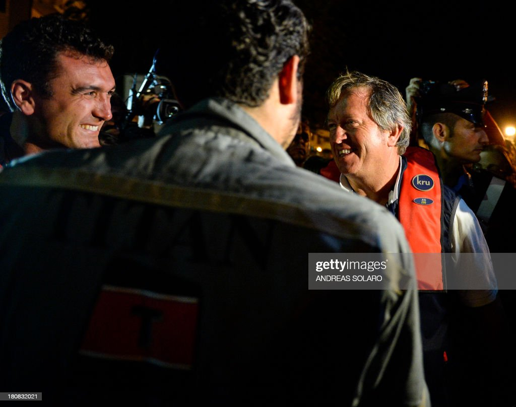 South African Nick Sloan (R) , senior salvage master of Titan-Micoperi, smiles with workers following the rotation of the wreck of Italy's Costa Concordia cruise ship on September 17, 2013 near the harbour of Giglio Porto. Salvage operators in Italy lifted the Costa Concordia cruise ship upright from its watery grave off the island of Giglio in the biggest ever project of its kind. The ship's horn sounded for the first time since the January 13, 2012 tragedy, its sound mixing with applause and cheers in the port in a dramatic climax to the massive salvage operation. Local residents and survivors spoke of an eerie feeling as the ship rose, saying the sight reminded them of the tragedy that claimed 32 lives.