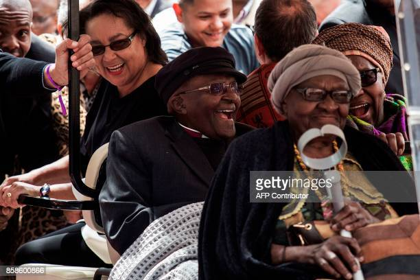 South African Nobel Peace Prize laureate Archbishop Desmond Tutu reacts as he arrives to attend the unveiling ceremony of the 'Arch for the Arch' as...