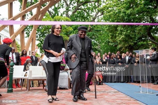 South African Nobel Peace Prize laureate Archbishop Desmond Tutu accompanied by Cape Town Mayor Patricia De Lille gets ready to cut the ribbon to...