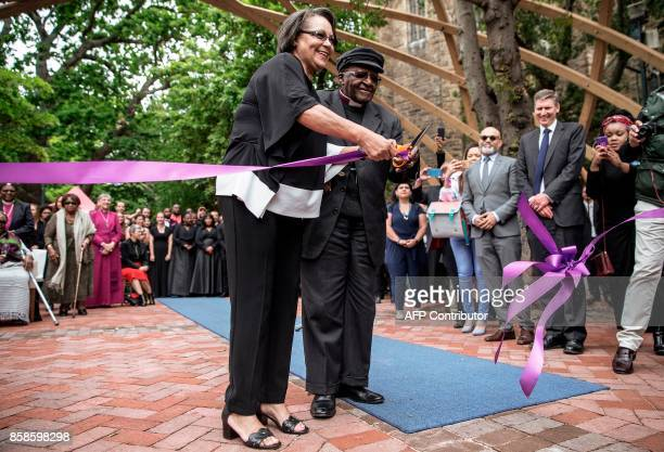 South African Nobel Peace Prize laureate Archbishop Desmond Tutu accompanied by Cape Town Mayor Patricia De Lille cuts the ribbon to unveil the 'Arch...