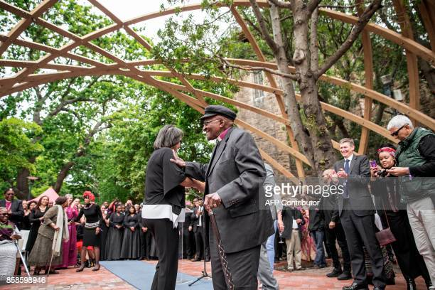 South African Nobel Peace Prize laureate Archbishop Desmond Tutu accompanied by Cape Town Mayor Patricia De Lille reacts after cutting the ribbon to...