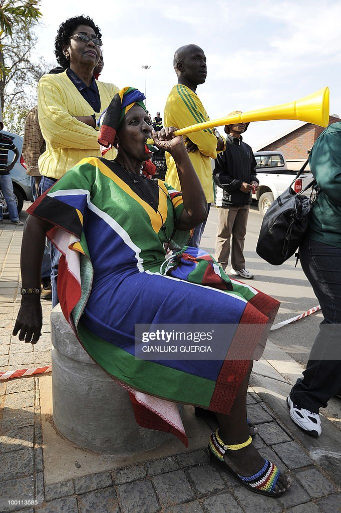 A South African old woman dressed with the country's colours poses as she blows her Vuvuzela on May 21, 2010 during the official celebration marking 20 days ahead of the FIFA WC2010 kick off at Vilakazi street in Soweto, South Africa. South Africa will host the FIFA World Cup from the 11 of June to the 11 of July, 2010.