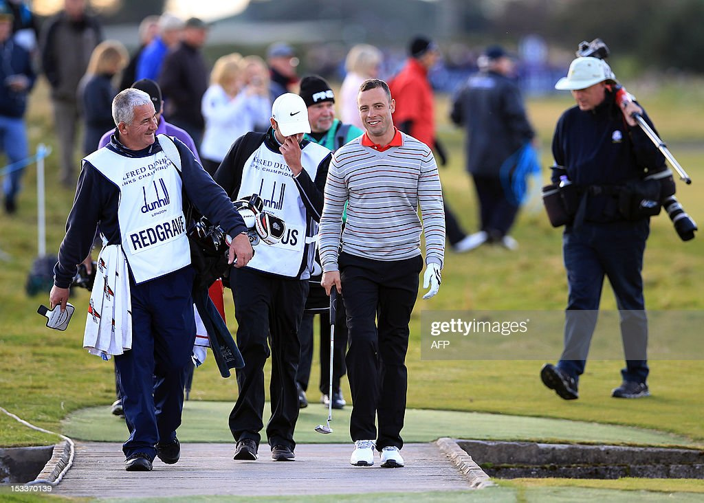 South African Olympian and Paralympian Oscar Pistorius (R) walks up the eighteenth during day one of the Alfred Dunhill Links Championship at Carnoustie, Scotland, on October 4, 2012.