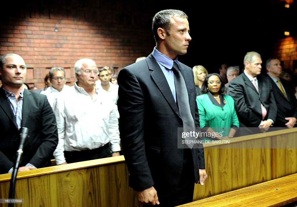 South African Olympic sprinter Oscar Pistorius (C) appears on February 19, 2013 at the Magistrate Court in Pretoria as he father Henke (2nd L) and brother Carl (L) attend. Pistorius battled to secure bail as he appeared on charges of murdering his model girlfriend Reeva Steenkamp on February 14, Valentine's Day. South African prosecutors will argue that Pistorius is guilty of premeditated murder in Steenkamp's death, a charge which could carry a life sentence.