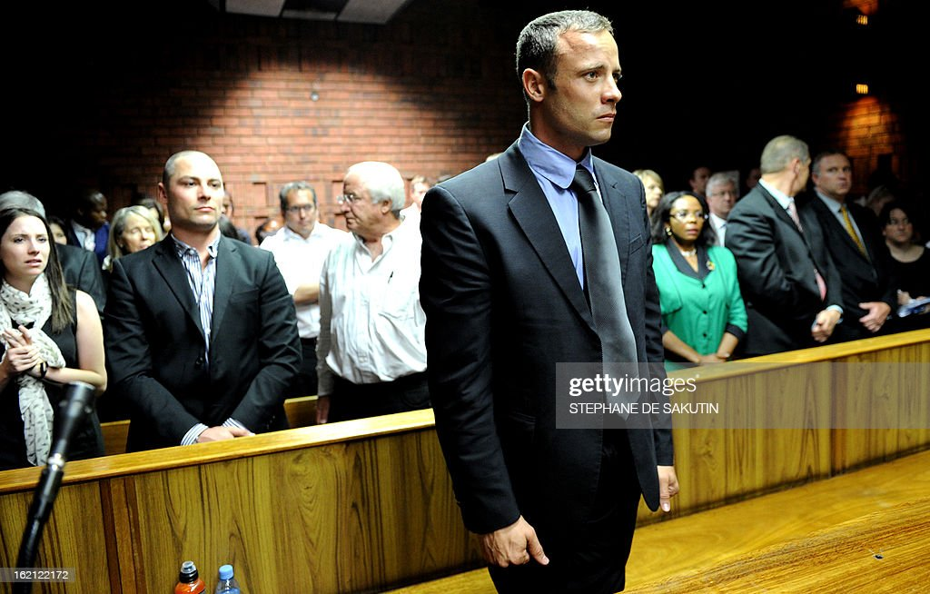 South African Olympic sprinter Oscar Pistorius (C) appears on February 19, 2013 at the Magistrate Court in Pretoria as he father Henke (3rd L), brother Carl (2nd L) and sister Aimee (L) attend. Pistorius battled to secure bail as he appeared on charges of murdering his model girlfriend Reeva Steenkamp on February 14, Valentine's Day. South African prosecutors will argue that Pistorius is guilty of premeditated murder in Steenkamp's death, a charge which could carry a life sentence. AFP PHOTO / STEPHANE DE SAKUTIN