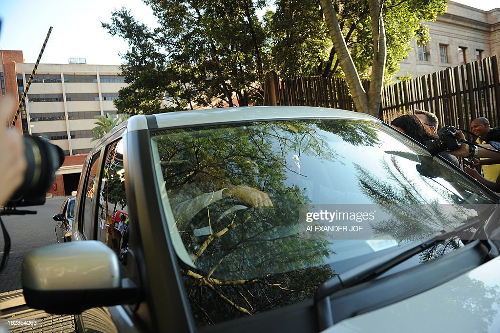 South African Olympic sprinter Oscar Pistorius (hidden) leaves the courthouse in a car in Pretoria on February 22, 2013 after being freed on bail by a magistrate, pending a high-profile trial for killing his girlfriend Reeva Steenkamp. AFP PHOTO / ALEXANDER JOE