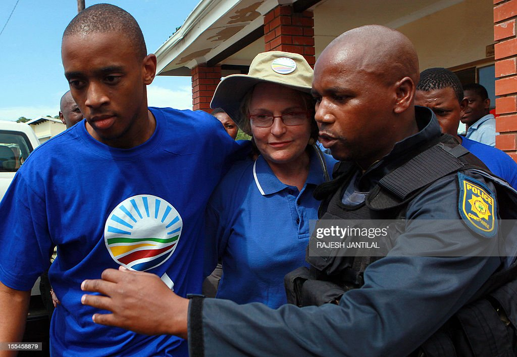 South African opposition Democratic Alliance (DA) leader Helen Zille is whisked away by security and members of the South African Police Service 's member after she laid a charge against ANC supporters not allowing Zille to enter President Jacob Zuma's private residence in Nkandla some 178 kilometres north of Durban on November 4, 2012 .The DA would inspect roads around the property and attempt to enter President Zuma's compound.Zuma's private home will reportedly feature underground bunkers,a clinic,a fire station,a special quarter for police and a helipad.The estimated costs for the current upgrade is set to cost 30 million US dollars.The DA has called for an investigations to the funding and upgrading of the Zuma's residence.