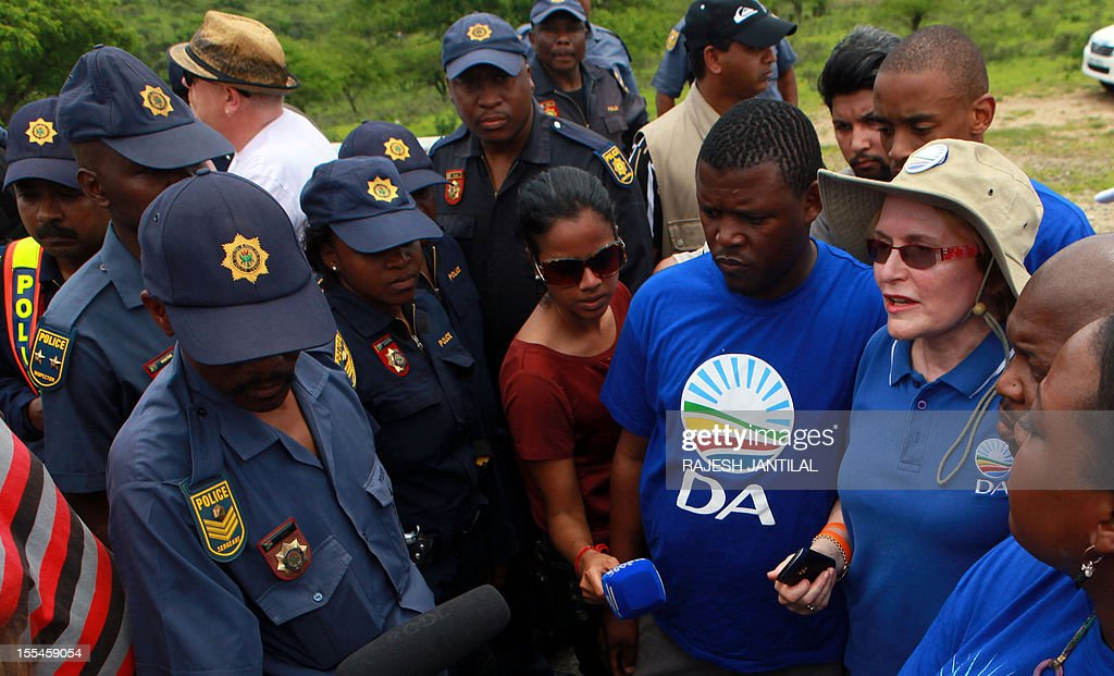 South African opposition Democratic Alliance ( DA) leader Helen Zille tries to negotiate with members of the South African Police Services (SAPS) preventing her and supporters from entering President Jacob Zuma's private residence in Nkandla, some 178 kilometres north of Durban, on November 4, 2012 .The DA would inspect roads around the property and attempt to enter President Zuma's compound.Zuma's private home will reportedly feature underground bunkers,a clinic,a fire station,a special quarter for police and a helipad.The estimated costs for the current upgrade is set to cost 30 million US dollars.The DA has called for an investigations to the funding and upgrading of the Zuma's residence.AFP PHOTO / RAJESH JANTILAL