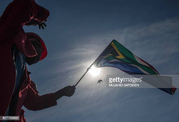 A South African opposition Economic Freedom Fighter party activist waves a national flag as he joins others shouting slogans as they gather in Church...