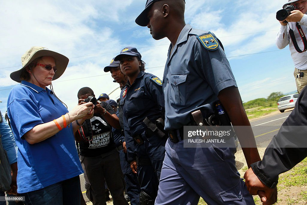 South African opposition leader Hellen Zille is blocked by members of the South African Police Services (SAPS) on her way to to President Jacob Zuma's private rural residence, at the centre of a row over a $29-million state-funded upgrade in Nkandla some 178 kilometres north of Durban on November 4, 2012. Police cited safety reasons for denying Zille and her six-member delegation passage to Zuma's homestead, where they wanted to inspect how public money was used to fund the president's private property. Supporters of the ruling African National Congress formed a barricade near the home, which is a cluster of modern thatched-roof Zulu huts.