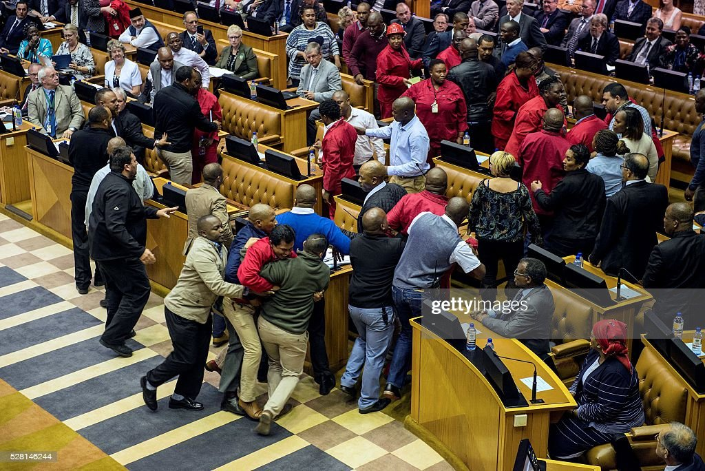 South African opposition party Economic Freedom Fighters MPs are pushed out of a parliament session during the South African president's budget speech in Cape Town on May 4, 2016. Fists flew in the South African parliament as security guards physically ejected leftist opposition lawmakers in the latest outbreak of political drama over the troubled presidency of Jacob Zuma. / AFP / -