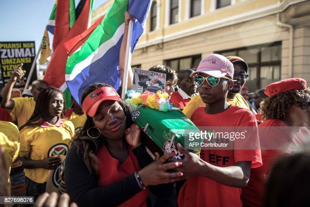 South African opposition party members carry a mocked up coffin with a photograph of Jacob Zuma in Cape Town on August 8 ahead of a Motion of no...