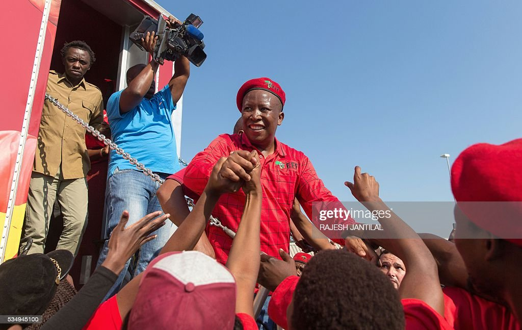 South African opposition radical leftist party Economic Freedom Fighters ( EFF) leader Julius Malema is greeted by supporters during an official local election campaign launch at the Esikhawini Shopping Centre on May 28, 2016 south of Durban, South Africa. Malema and his supporters were attacked by a group of African National Congress ( ANC) supporters who hurled stones ans rocks as Malema took to the podium. The South African Poilce Services ( SAPS) fired rubber bullets at the ANC supporters. / AFP / RAJESH