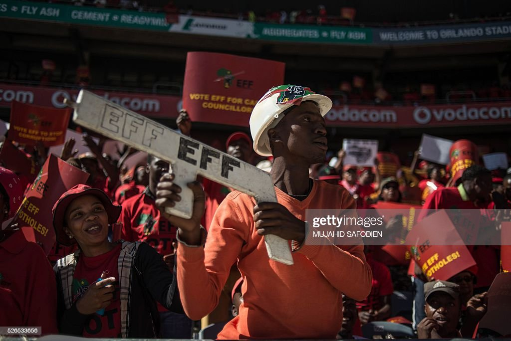 South African opposition radical party Economic Freedom Fighters supporter holds a EFF sign during the official local election manifesto launch at Soweto's Orlando Stadium in Johannesburg on April 30, 2016, targeting white privilege and the ruling African National Congress. Around 40,000 people turned Orlando stadium in Soweto into a sea of red as supporters roared their approval of fiery EFF leader Julius Malema's promises to seize white-owned land without compensation and nationalise the banks. / AFP / MUJAHID