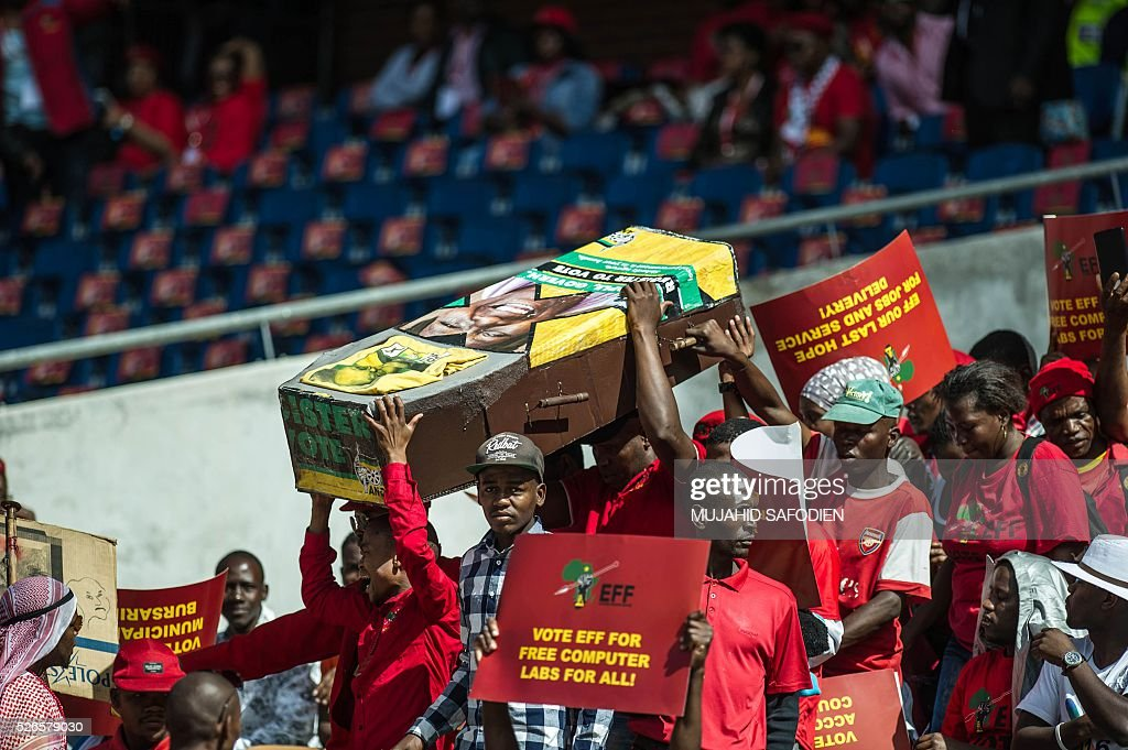 South African opposition radical party Economic Freedom Fighters supporters parade a mock casket with ruling party African National Congress symbols during the EFF official local election manifesto launch at Soweto's Orlando Stadium in Johannesburg on April 30, 2016. Around 40,000 people turned Orlando stadium in Soweto into a sea of red as supporters roared their approval of fiery EFF leader Julius Malema's promises to seize white-owned land without compensation and nationalise the banks, targeting white privilege and the ruling African National Congress. / AFP / MUJAHID