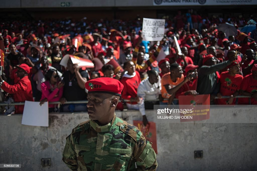 South African opposition radical party Economic Freedom Fighters supporters cheer as they attend the official local election manifesto launch at Soweto's Orlando Stadium in Johannesburg on April 30, 2016, targeting white privilege and the ruling African National Congress. Around 40,000 people turned Orlando stadium in Soweto into a sea of red as supporters roared their approval of fiery EFF leader Julius Malema's promises to seize white-owned land without compensation and nationalise the banks. / AFP / MUJAHID