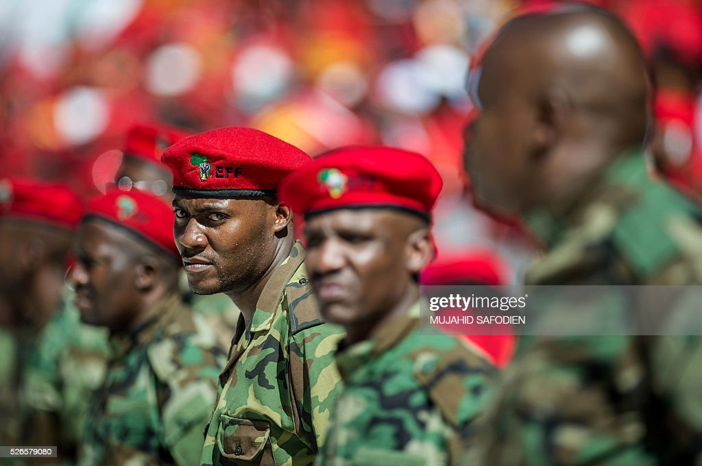 South African opposition radical party Economic Freedom Fighters members dressed in military fatigues stand in attentions during the EFF official local election manifesto launch at Soweto's Orlando Stadium in Johannesburg on April 30, 2016. Around 40,000 people turned Orlando stadium in Soweto into a sea of red as supporters roared their approval of fiery EFF leader Julius Malema's promises to seize white-owned land without compensation and nationalise the banks, targeting white privilege and the ruling African National Congress. / AFP / MUJAHID