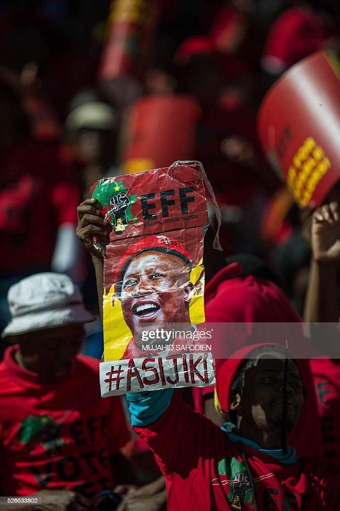 South African opposition radical party Economic Freedom Fighters supporters hold EFF signs as they attend the official local election manifesto launch at Soweto's Orlando Stadium in Johannesburg on April 30, 2016, targeting white privilege and the ruling African National Congress. Around 40,000 people turned Orlando stadium in Soweto into a sea of red as supporters roared their approval of fiery EFF leader Julius Malema's promises to seize white-owned land without compensation and nationalise the banks. / AFP / MUJAHID
